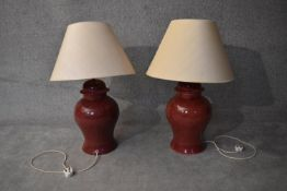 A large pair of deep red glazed table lamps of bulbous form with cream shades. H.80cm (inc. shade)