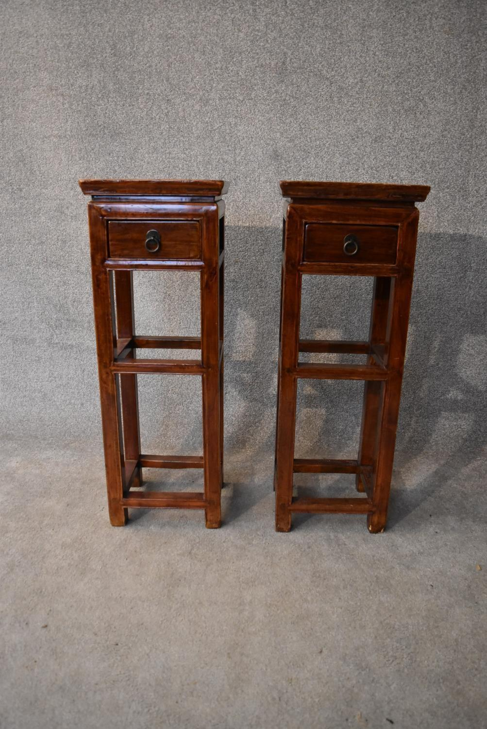 A pair of Chinese hardwood urn stands fitted frieze drawers. H.86x32cm