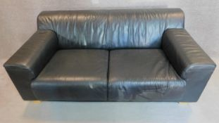 An Italian black leather sofa on solid block feet. 73x177x97cm (bought from Heal's).