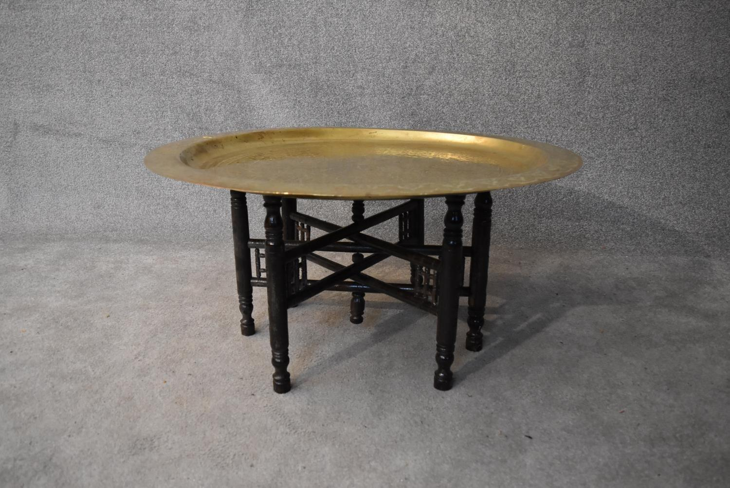 An Eastern brass topped table on folding hardwood stand. H.45xDia.90cm