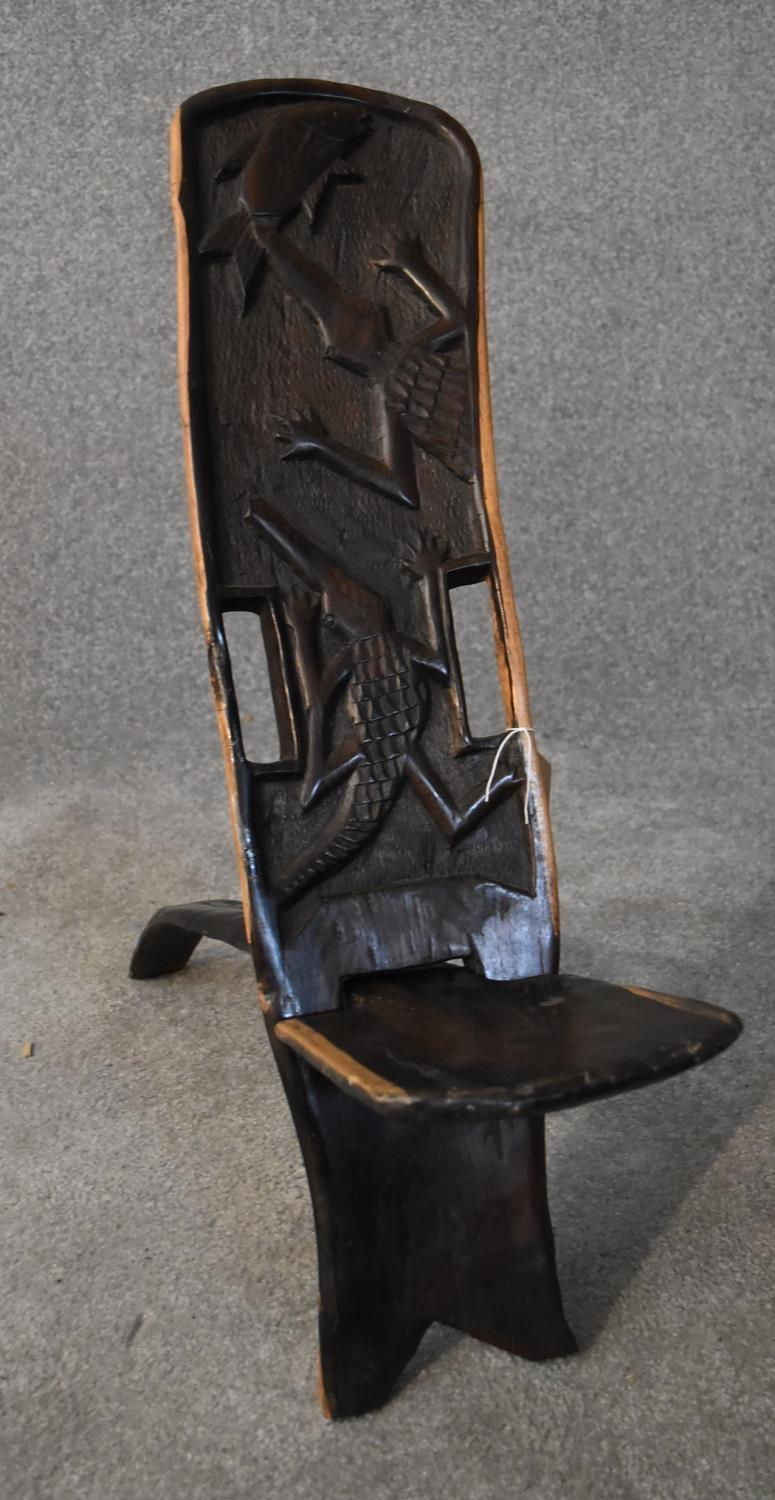 An African carved hardwood two part palaver chair with relief alligator detailing. H.80x20cm