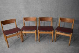 A set of four mid 20th century teak dining chairs in faux grained leather burgundy upholstery H.