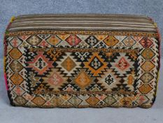 A footstool fully upholstered in kilim. H.52 W.92 D.40cm