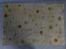 A contemporary floral rug with repeating flower motifs on a beige field 188x128cm