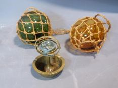 Two antique fishing floats and a brass ship's compass ashtray. H14cm.