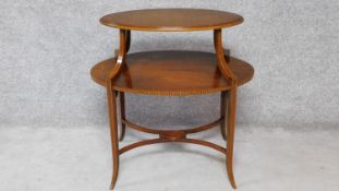 An Edwardian mahogany and satinwood inlaid two tier oval topped etagere on swept square