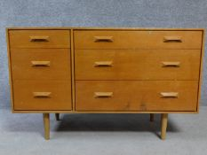 A 1970's vintage teak chest of three graduating long drawers flanked by three short drawers raised