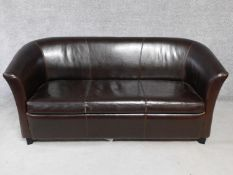 A tan leather two seater tub shaped sofa. H.78 W.173 D.83cm