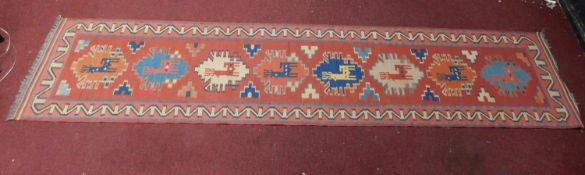 A Kazak style runner, repeating reindeer motifs on a terracotta field within geometric border