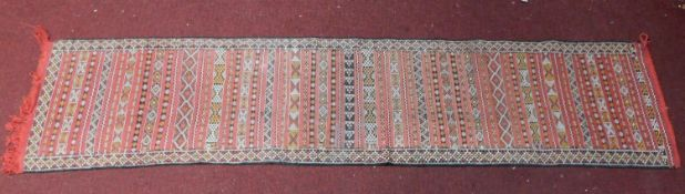 A Kilim style runner with repeating geometric design on red ground, fringed 290x65cm