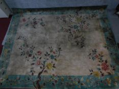 A large Chinese rug with allover bird and flower motifs and spandrels on a mink field encompassed by