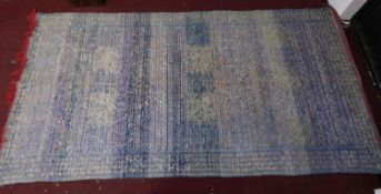 A double sided Kilim style rug with narrow geometric bands on blue field with red fringes 186x356cm