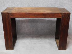 An Eastern hardwood console table with reeded block supports. H.77 W.120 D.45cm