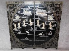 A Japanese mother of pearl and bone inlaid black lacquered three fold and four panel screen. H.183