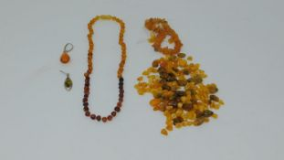 A collection of antique amber necklaces and beads, including two odd amber and silver earrings, a
