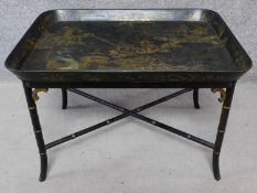 A black lacquered Chinoiserie decorated papier mache coffee table on bamboo stretchered supports.