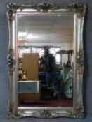 A large silver rococo framed bevelled wall mirror. 183x123cm