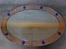 An Art Deco peach glass framed wall mirror with blue glass insets. 128x98cm
