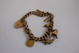 A 9ct GOLD AND YELLOW METAL CHARM BRACELET, charms include an 1853 USA $1