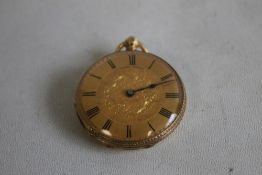 A YELLOW METAL FOB WATCH (marked 18ct), gilt engraved dial with black Roman Numeral markings.
