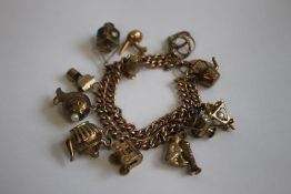 A 9CT GOLD AND YELLOW METAL CHARM BRACELET, charms include a railway lamp, kettle and fish etc.