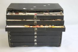 A LARGE QUANTITY OF POCKET WATCH PARTS STORED IN A NINE DRAWER CABINET, to include movements,