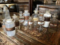 A COLLECTION OF TEN LATE 19TH / EARLY 20TH CENTURY GLASS APOTHECARY / CHEMISTS BOTTLES, ALL WITH