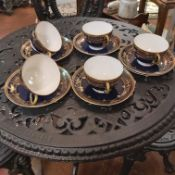 AN EARLY 20TH CENTURY DECORATIVE SET OF ROYAL WORCESTER CUPS AND SAUCERS, HEAVILY GILDED WITH ENAMEL