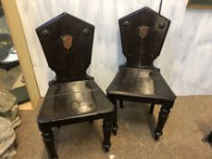 A PAIR OF REGENCY ARMORIAL HALL CHAIRS CIRCA 1820, BOTH WITH ORIGINAL PAINTED GILT ARMORIAL