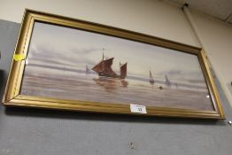 A GILT FRAMED AND GLAZED WATERCOLOUR DEPICTING SAIL SHIPS AT SEA INDISTINCTLY SIGNED LOWER LEFT