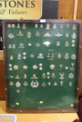 AN OAK DISPLAY CASE CONTAINING A DISPLAY OF VINTAGE MILITARY BADGES AND BUTTONS ETC.