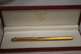 A CARTIER GOLD PLATED BALL POINT PEN IN FITTED BOX, with guarantee card and outer card slip box