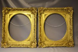 A PAIR OF MID 19TH CENTURY DECORATIVE GILT FRAMES WITH CORNER EMBELLISHMENTS AND OVAL SPANDRELS,