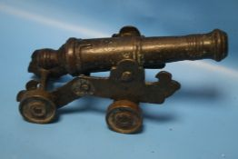 A SMALL ANTIQUE SIGNAL CANNON ON SHEET METAL CARRIAGE