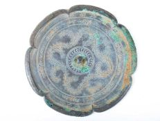 A Chinese bronze mirror, Tang, 中国,铜镜一个,唐代 the six lobes enclosing relief tendrils and with three
