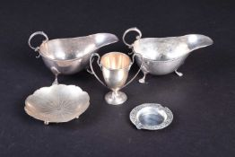 A small group of silver items, comprising two sauce boats, a miniature trophy, a small ashtray and a