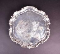 An Edwardian silver salver, Birmingham 1910 by Elkington & Co, of scroll edge form with engraved