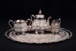 An Indian white metal three-piece teaset and conforming oval tray, 20th century, each decorated with