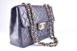 Chanel. A classic single flap black leather quilted handbag, with double gold tone chain and leather