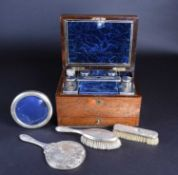 A matched silver-backed dressing table set, comprising a mirror and two brushes, various dates and
