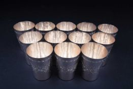 A set of twelve Continental silver beakers, each stamped 'Silver', with engraved floral