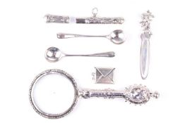 A white metal mounted magnifying glass, with cherub decoration, together with a pair of silver