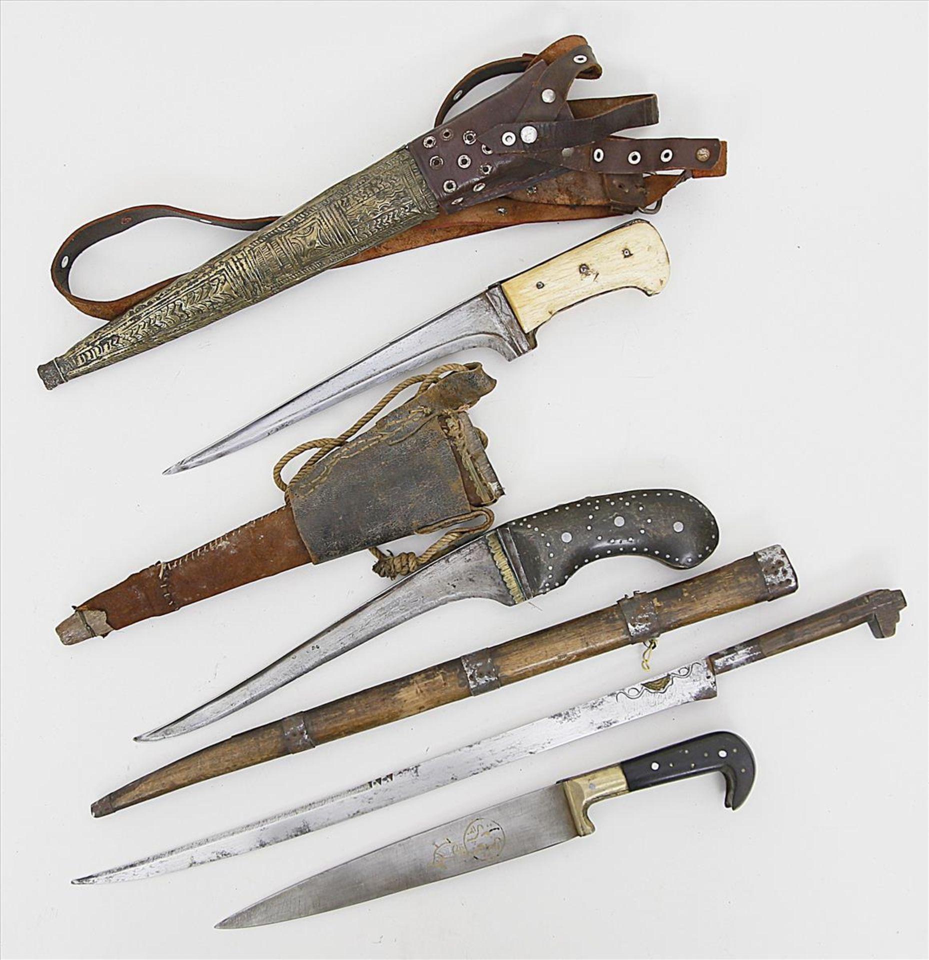 Los 1556 - Drei Khyber- und ein Flyssa-Messer.Einschneidige Eisenklingen. Geschnitzte Holz- bzw. Beingriffe mit