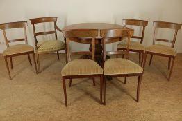 Serie van 6 mahonie stoelen (een afwijkend) en een mahonie coulissentafel op kolompoot uitlopend