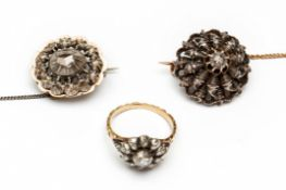 Twee zilveren en gouden broches en een ring,