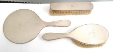 A London silver dressing set by DCBs, comprising of a hand mirror and two brushes, dated 1955