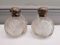 A pair of silver topped cut glass scent bottles 12cm in height