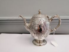 A Marshall and sons Edinburgh silver tea pot having repousse/chased c scroll and foliage design,