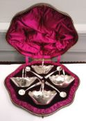 Cased set of four Victorian silver salts and spoons in the style of handled baskets with scalloped