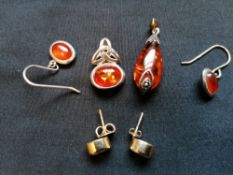 A collection of amber jewellery to include two silver and amber pendants, a pair of silver and amber